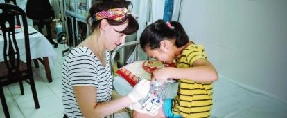 Projects Abroad female intern is seen making a child laugh during a routine check up on her nursing work experience in Vietnam.
